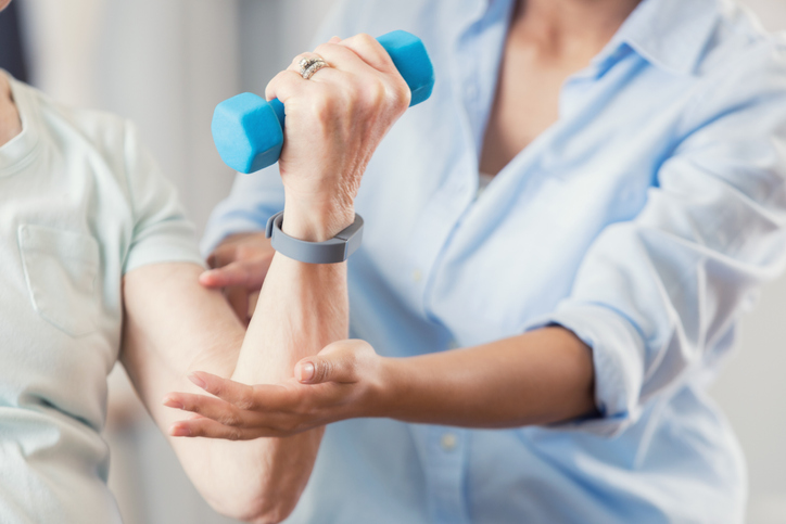 Physical therapist works with senior woman. The patient is using a hand weight.