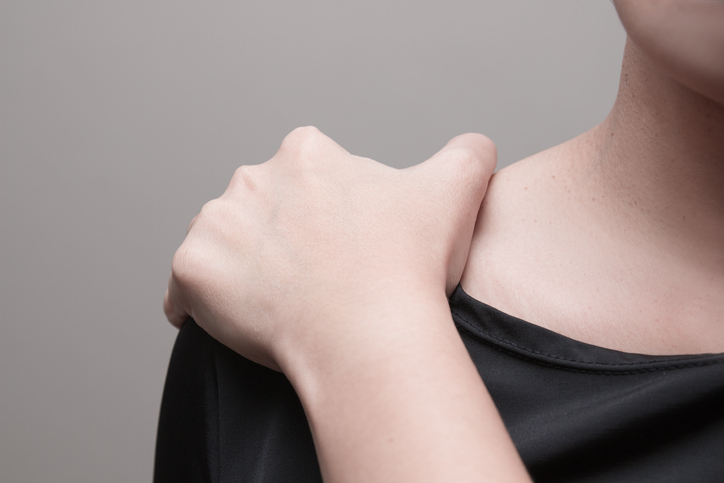 Young woman suffering from pain in shoulder.
