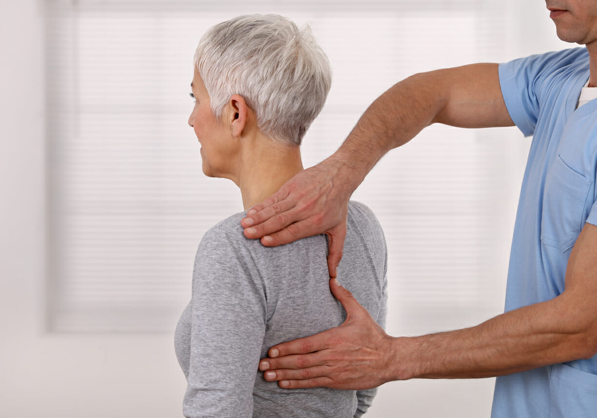 Mature Woman having chiropractic back adjustment.