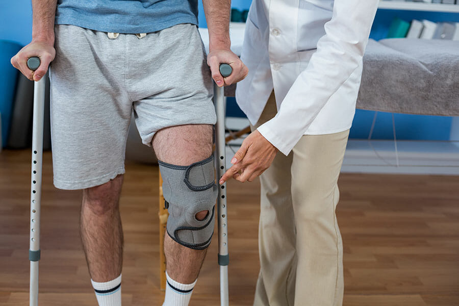 car accident treatment and rehabilitation in oakville patient with crutches and knee brace being helped by female doctor