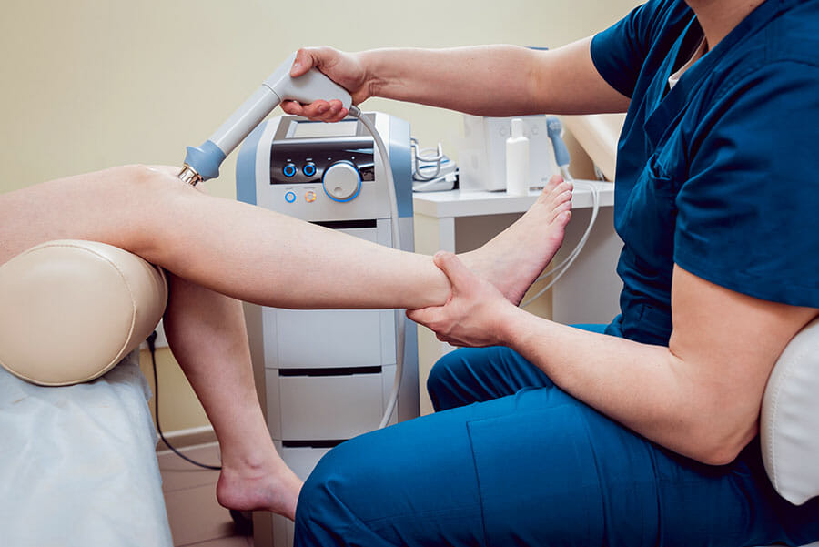 Shockwave therapy Oakville, doctor holding shockwave gun against female patients knee