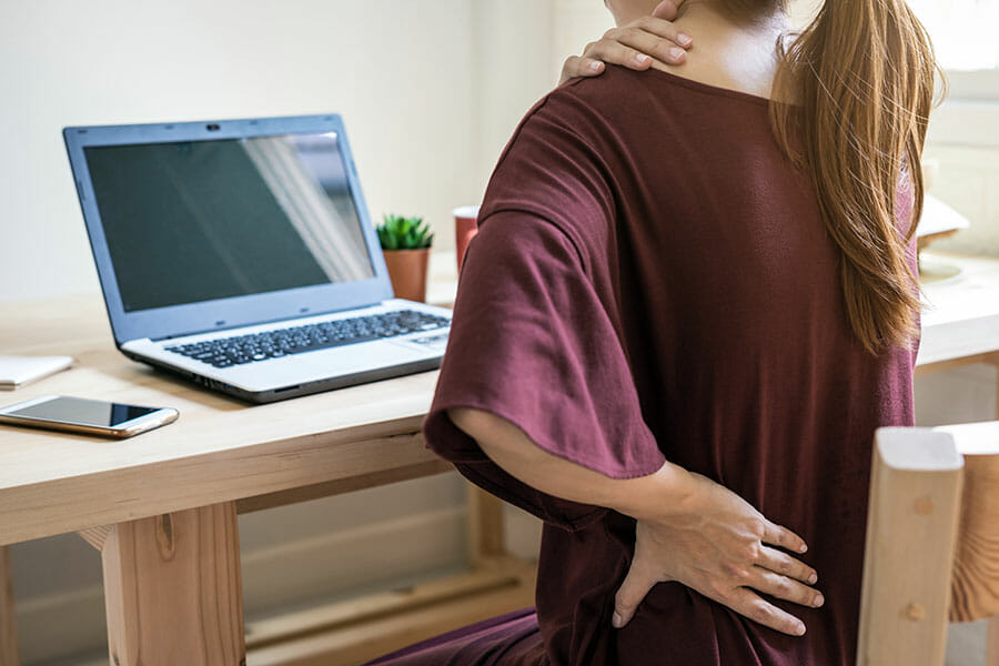 female at computer holding left side of neck and back, if hurt at work should call our wsib clinic in oakville