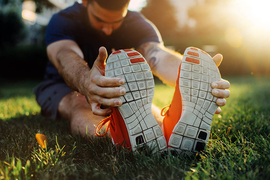 Custom Orthotics Oakville man stretching his hamstrings with his shoes after a run
