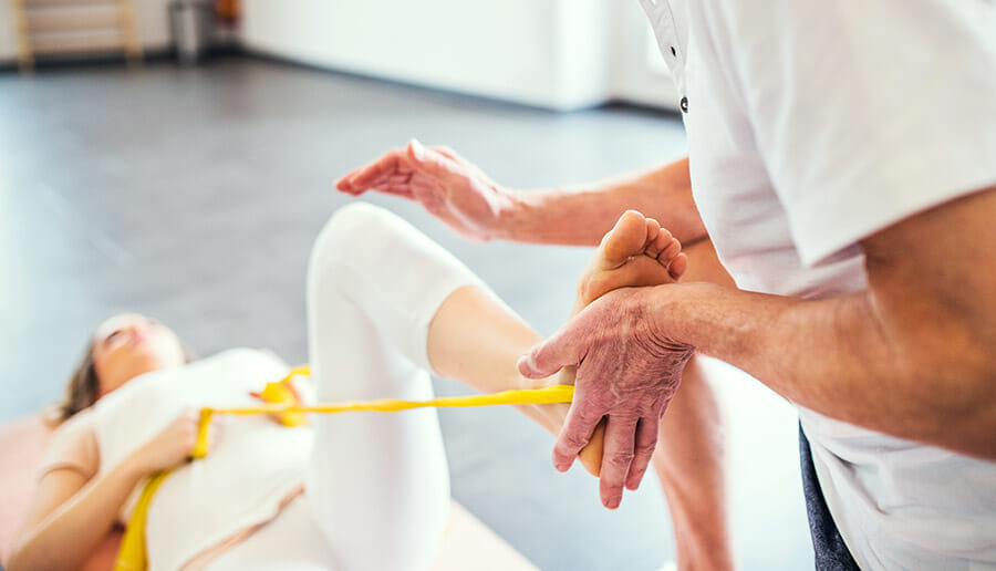 Oakville Physiotherapist using a band to help a patient on her back with a foot complaint
