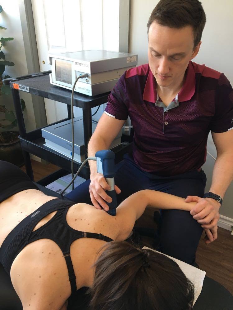 Oakville chiropractor using shockwave treatment on shoulder