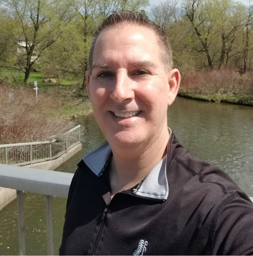 Oakville Chiropractor, male standing on bridge by a river, nice fall day